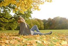 Adolescente que miente en parque del otoño Imagen de archivo libre de regalías