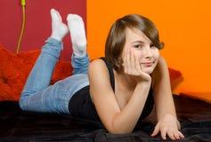 Adolescente que miente en su cama Fotos de archivo