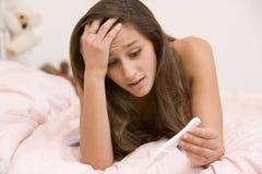 Adolescente que miente en su cama Foto de archivo