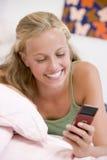 Adolescente que miente en su cama usando el teléfono móvil Fotografía de archivo libre de regalías