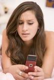 Adolescente que miente en su cama usando el teléfono móvil Fotografía de archivo