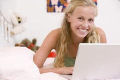 Adolescente que miente en su cama usando la computadora portátil Fotos de archivo