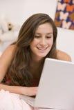 Adolescente que miente en su cama usando la computadora portátil Imagen de archivo libre de regalías
