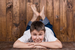 Adolescente que miente en su estómago Contra la perspectiva de los tablones de madera Foto de archivo