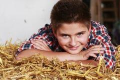 Adolescente que miente en una bala de la paja Foto de archivo libre de regalías
