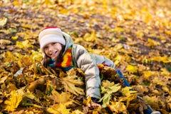 Adolescente que miente y que juega en las hojas, felices, Foto de archivo libre de regalías
