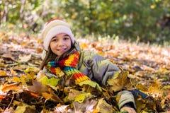 Adolescente que miente y que juega en las hojas, felices Imagenes de archivo