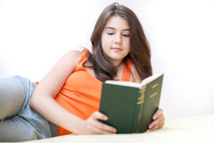 Adolescente que miente y que lee un libro Fotos de archivo libres de regalías