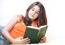 Adolescente que miente y que lee un libro Foto de archivo libre de regalías