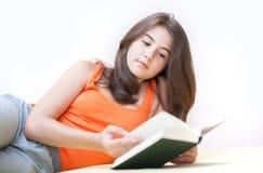 Adolescente que miente y que lee un libro Fotografía de archivo