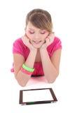 Adolescente que miente y que usa la PC de la tablilla Imágenes de archivo libres de regalías
