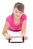 Adolescente que miente y que usa la PC de la tablilla sobre blanco Imagen de archivo libre de regalías