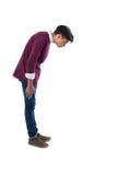 Adolescente que mira abajo contra el fondo blanco Imágenes de archivo libres de regalías