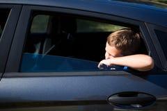 Adolescente que mira de la ventanilla del coche abierta Foto de archivo libre de regalías