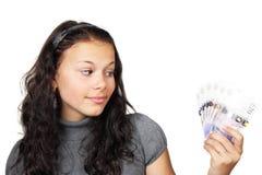 Adolescente que mira el dinero Imagen de archivo