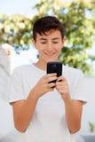Adolescente que mira el móvil Imagen de archivo libre de regalías
