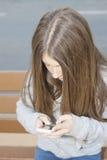 Adolescente que mira el móvil Fotografía de archivo