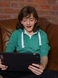 Adolescente que mira el ordenador de la tablilla Fotos de archivo