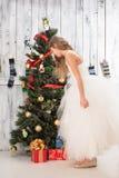 Adolescente que mira el regalo de Navidad cerca de árbol del Año Nuevo Fotografía de archivo libre de regalías