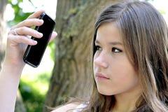 Adolescente que mira el teléfono celular móvil Fotos de archivo
