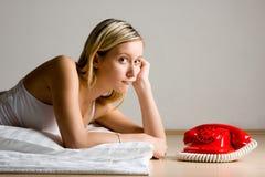 Adolescente que mira el teléfono rojo Fotos de archivo libres de regalías