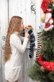 Adolescente que mira en calcetines del Año Nuevo y de la Navidad Imágenes de archivo libres de regalías