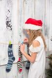 Adolescente que mira en calcetines del Año Nuevo y de la Navidad Fotos de archivo
