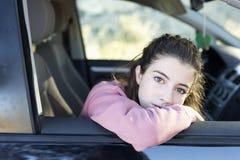 Adolescente que mira hacia fuera la ventana de su coche Foto de archivo libre de regalías