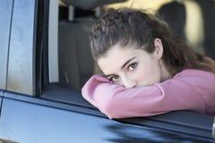 Adolescente que mira hacia fuera la ventana de su coche Fotografía de archivo