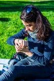 Adolescente que mira su reloj de la mano - mirada del tiempo Imagen de archivo libre de regalías