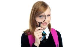 Adolescente que mira a través de una lupa Fotografía de archivo