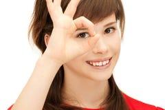 Adolescente que mira a través del agujero de los fingeres Foto de archivo libre de regalías