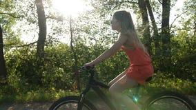 Adolescente que monta en bicicleta en el camino rural en la oscuridad almacen de video