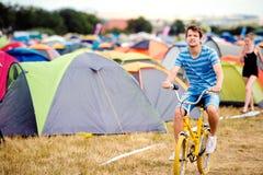 Adolescente que monta la bici amarilla en el festival de música del verano Imágenes de archivo libres de regalías