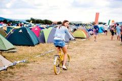 Adolescente que monta la bici amarilla en el festival de música del verano Imagen de archivo