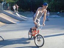 Adolescente que monta la bici en área que anda en monopatín en parque Imagenes de archivo
