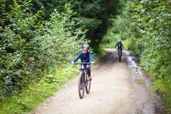 Adolescente que monta la bicicleta en el camino de la montaña Fotografía de archivo