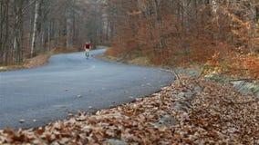 Adolescente que monta su bici en el camino forestal del otoño metrajes