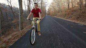 Adolescente que monta su bici en el camino forestal soleado del otoño cuesta abajo almacen de video