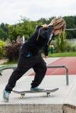 Adolescente que monta su monopatín Fotografía de archivo