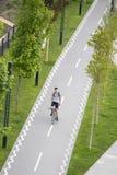 Adolescente que monta una bici en carril de bicicleta de la 'promenade' de Sava en la costa de Belgrado, desde arriba foto de archivo libre de regalías