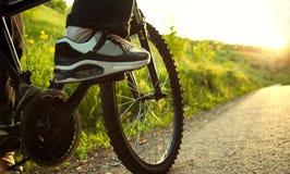 Adolescente que monta una bicicleta en el foco iluminado por el sol del verano del camino en wh Foto de archivo