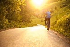 Adolescente que monta una bicicleta en el verano del camino iluminado por el sol Imagen de archivo