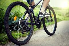 Adolescente que monta una bicicleta en el verano del camino iluminado por el sol Foto de archivo libre de regalías