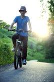Adolescente que monta una bicicleta en el verano del camino iluminado por el sol Imagen de archivo libre de regalías