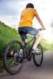 Adolescente que monta una bicicleta en el verano del camino iluminado por el sol Imágenes de archivo libres de regalías