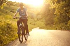 Adolescente que monta una bicicleta en el verano del camino iluminado por el sol Foto de archivo