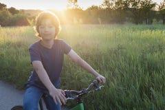 Adolescente que monta una bicicleta en el verano del camino iluminado por el sol fotografía de archivo