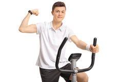 Adolescente que monta una bicicleta estática y que dobla su bíceps Imagenes de archivo