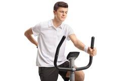 Adolescente que monta una bicicleta estática y que experimenta dolor de espalda Imagen de archivo